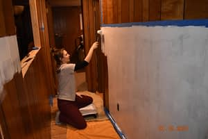 priming the hallway paneling before the wainscoting application